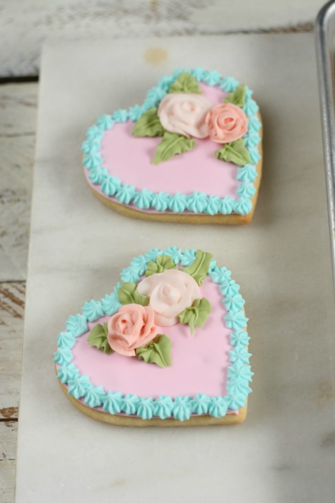 Heart sugar cookies with pale pink royal icing and sugar roses