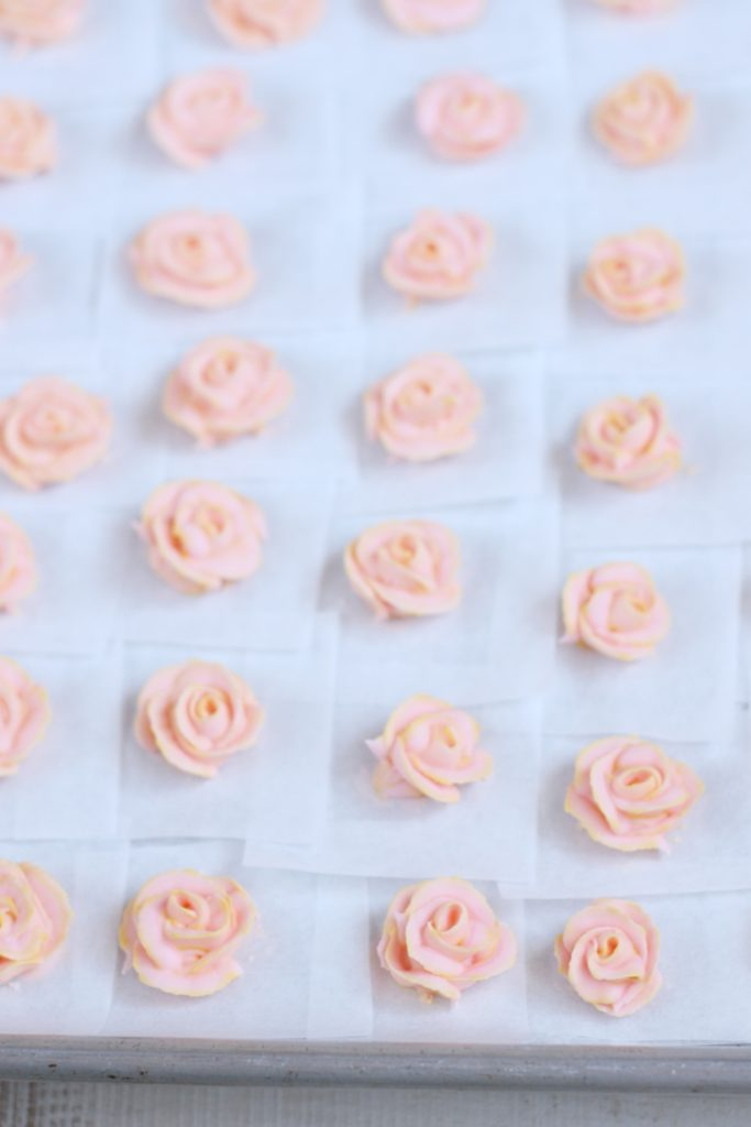 Pale pink royal icing roses on sheet pan