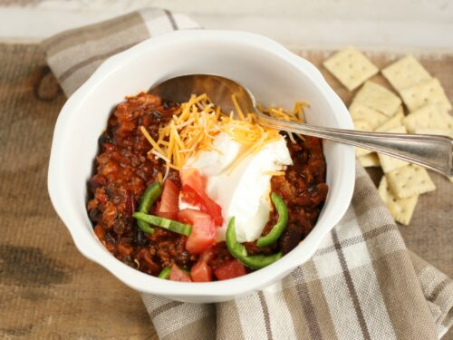 Hearty Chili in a white bowl topped with shredded cheddar cheese, slices of jalapeno peppers, and sour cream