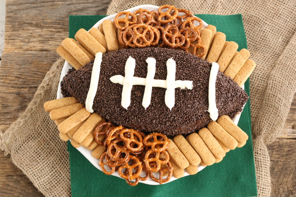 Brownie Batter football dip with chocolate sprinkles and vanilla frosting laces on plate with small pretzels and graham cracker sticks