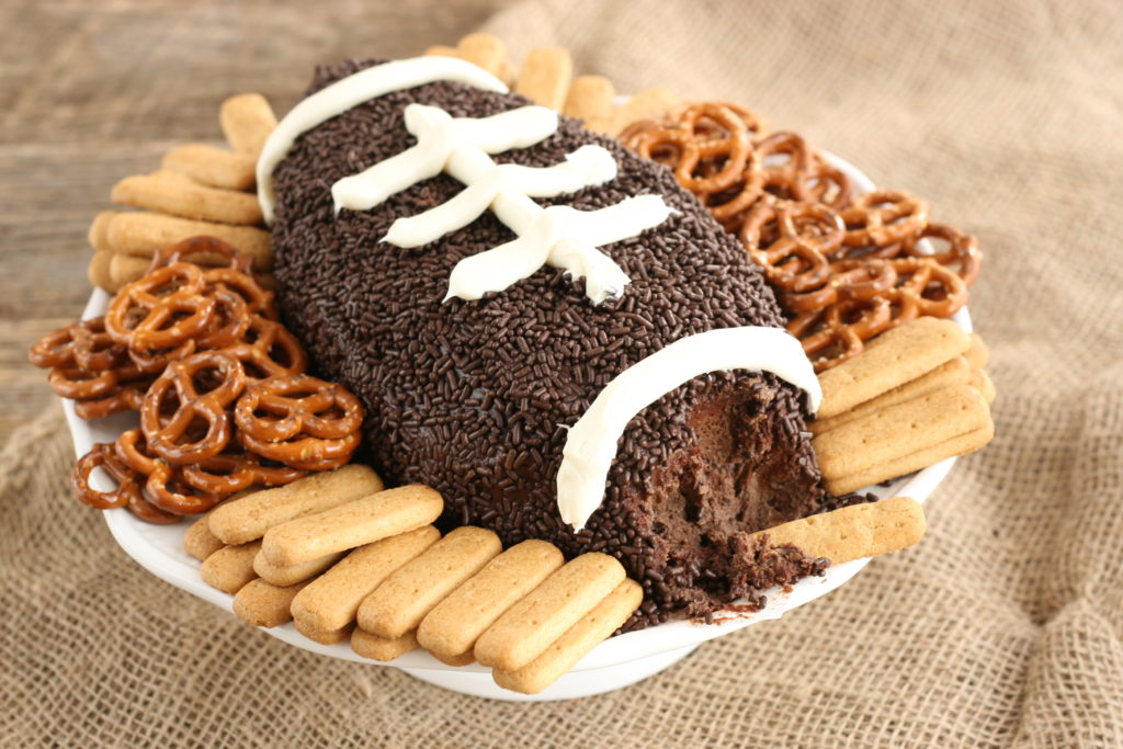 Brownie batter football dip with pretzels and graham cracker sticks with the end of football part way eaten