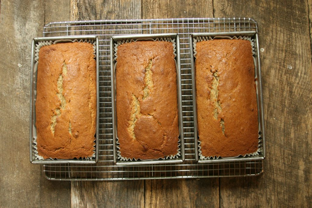 three loaves of pecan banana bread cooling on a baking rack.