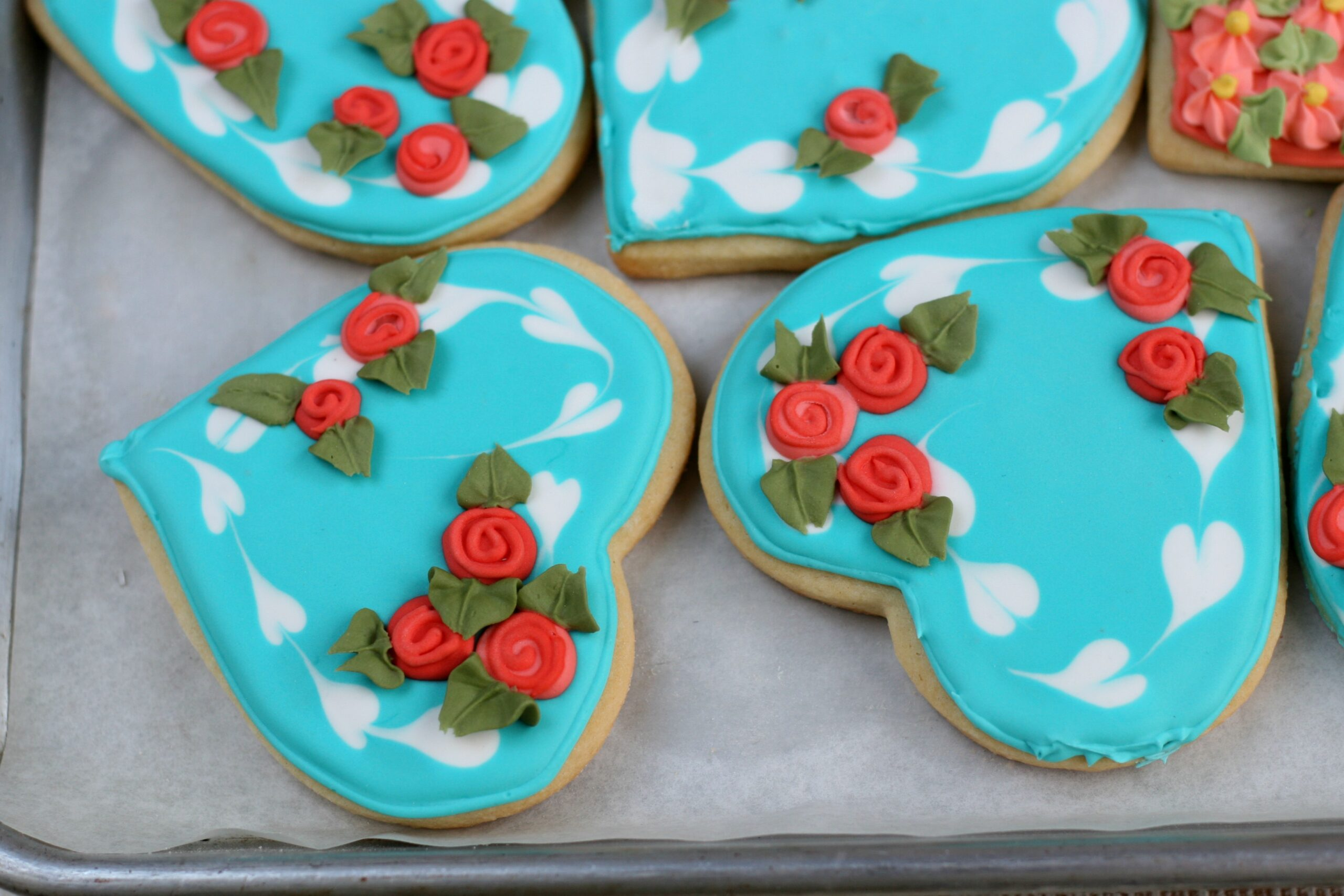 Teal color sugar cookies with red roses and leaf details with royal icing.