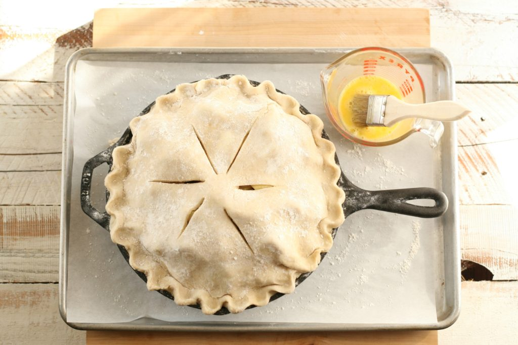 unbaked apple pie sitting on sheet pan with egg wash in glass measuring cup