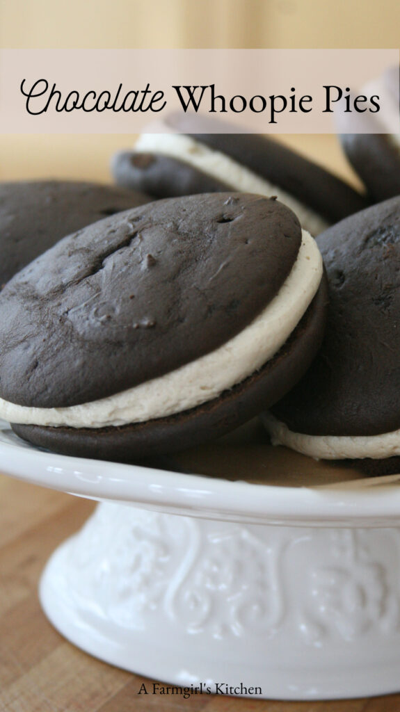 Chocolate whoopie pies on white ceramic footed cake dish