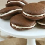 chocolate whoopie pies on white footed cake dish