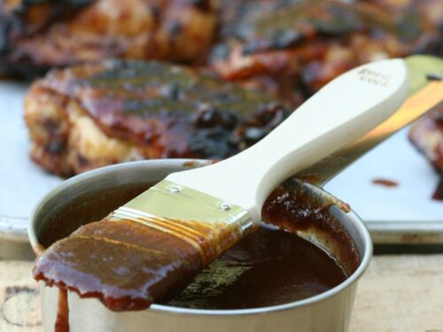 barbecue sauce in metal measuring cup with brush dripping barbecue sauce, chicken in background