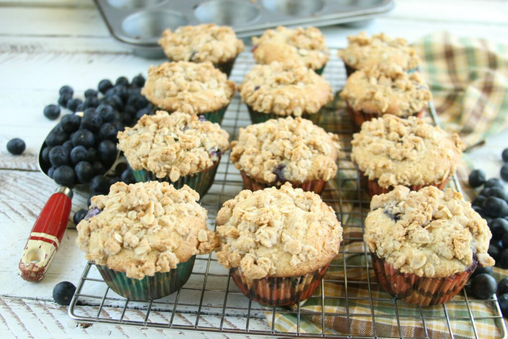 Freshly baked blueberry muffins cooling on a baking rack