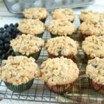 Blueberry muffins cooling on a baking rack with streusel topping