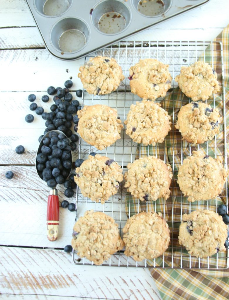 Blueberry muffins cooling on a baking rack, scoop of blueberries on side