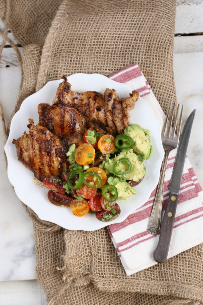 grilled chicken with avocado tomato salad and fork