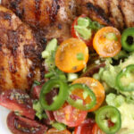 grilled chicken on small white plate with heirloom cherry tomato halves and avocado salad, topped with thin slices of jalapenos