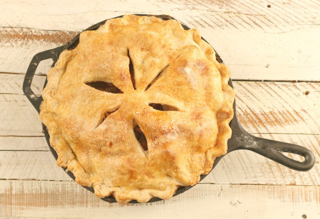 Baked apple pie with homemade crust in cast iron skillet