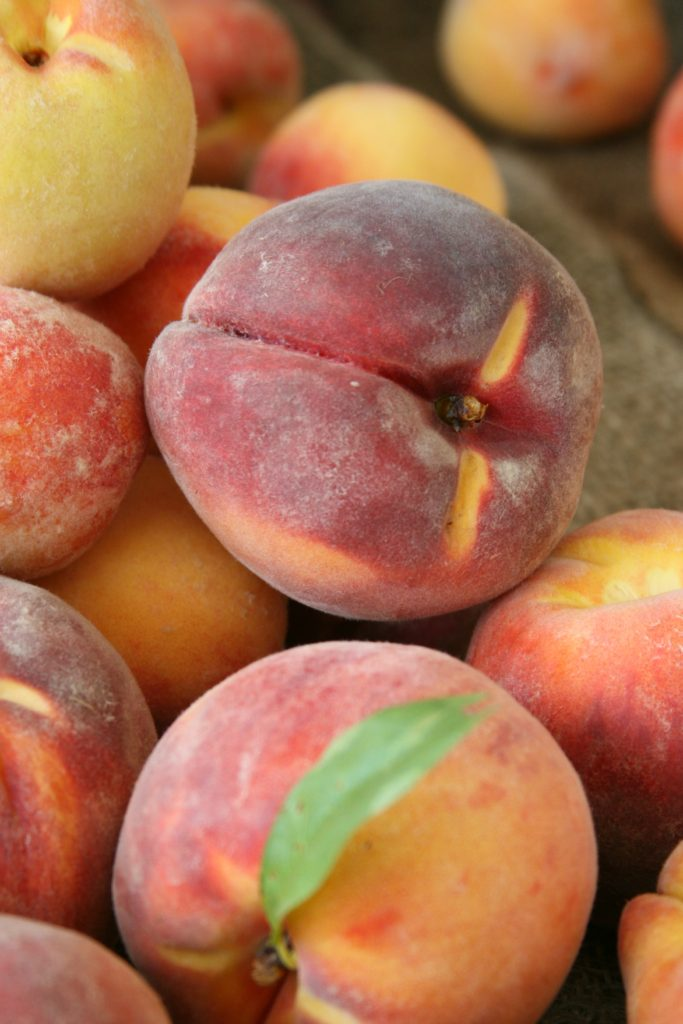 farm fresh peaches piled on each other at farmers market
