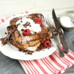 Chocolate brioche french toast on slate cutting board with red and white striped kitchen towel