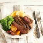 Get this amazing recipe for Citrus Garlic Marinated Flank Steak with steamed broccoli and heirloom cherry tomatoes. #recipes #steak