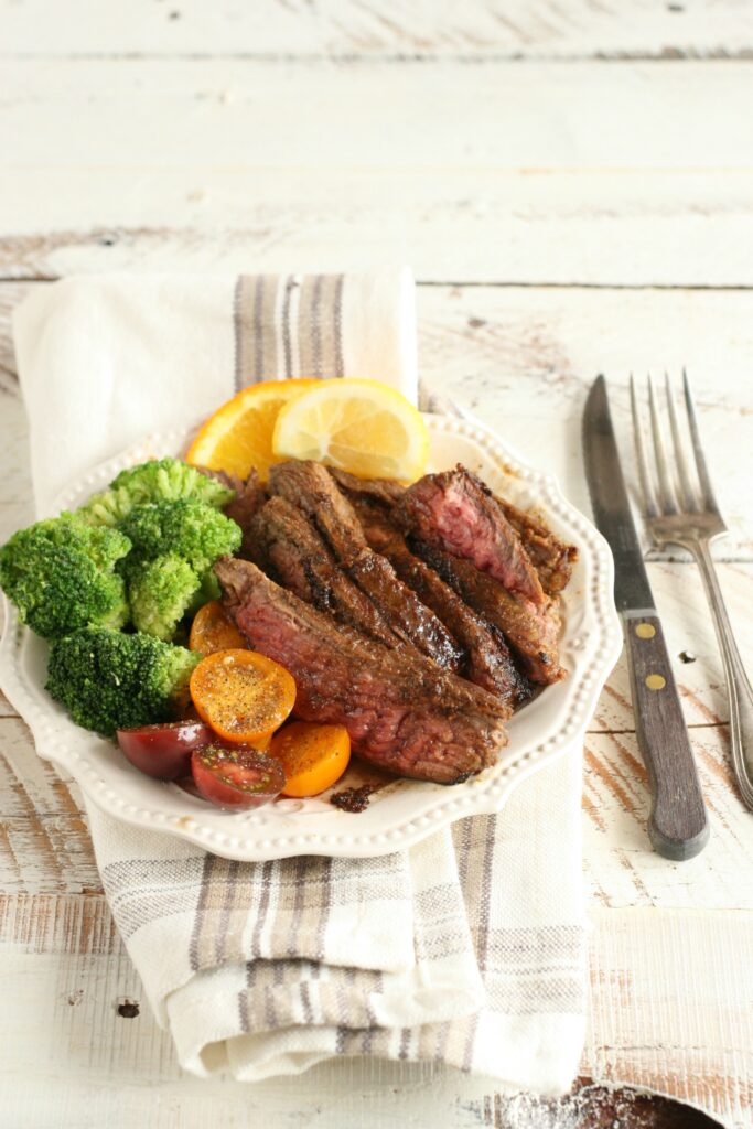 Citrus and Garlic Marinated Flank Steak on a plate with broccoli and cherry tomatoes