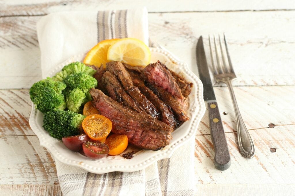 Slices of Citrus and Garlic Marinated Flank Steak on a white plate with broccoli