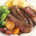 sliced flank steak on small white plate with cherry tomato halves, and slices of lemons