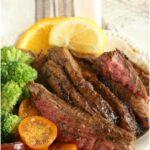 sliced flank steak on white plate with cherry tomato slices, fresh broccoli, lemon slices