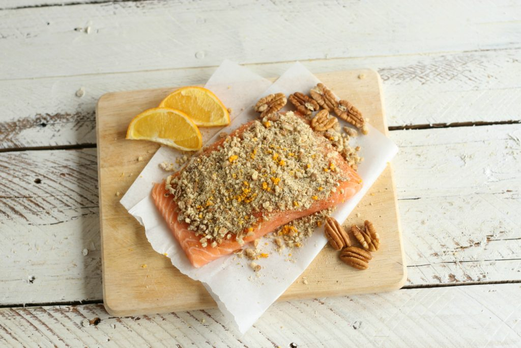 Uncooked Maple Pecan Crusted Salmon on wooden cutting board with pecans and orange slices