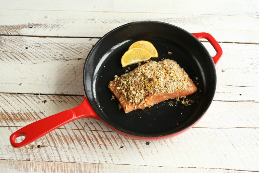 Maple Pecan Crusted Salmon in red enamel coated cast iron skillet cooking