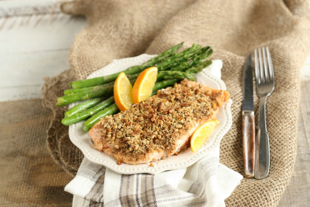 Maple Pecan Crusted Salmon on white plate with asparagus and orange wedges along with knife and fork to the right side of the plate