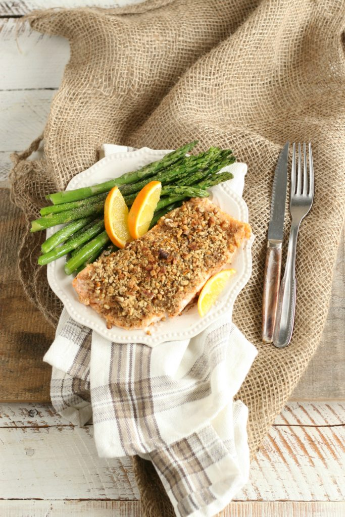 Maple Pecan Crusted Salmon with asparagus and wedges of oranges on white scallop edged plate sitting on a piece of burlap