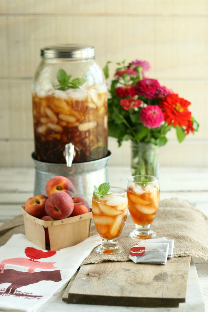 Homemade peach sweet tea in a glass drink dispenser