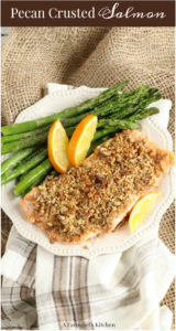maple pecan crusted salmon on a plate with orange slices and fresh asaragus