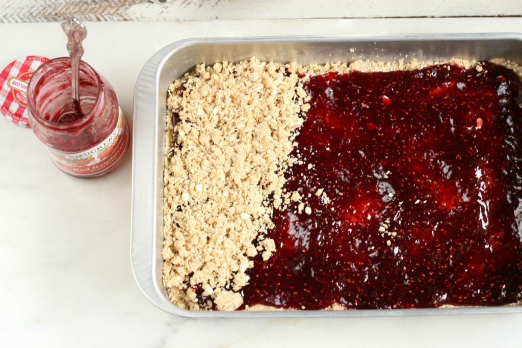 Raspberry Oatmeal Bars getting the final topping before baking