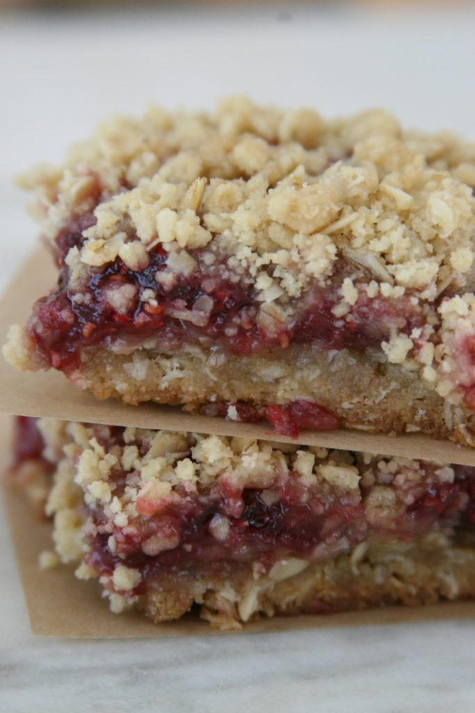 Raspberry oatmeal crumble bars sitting on top of each other