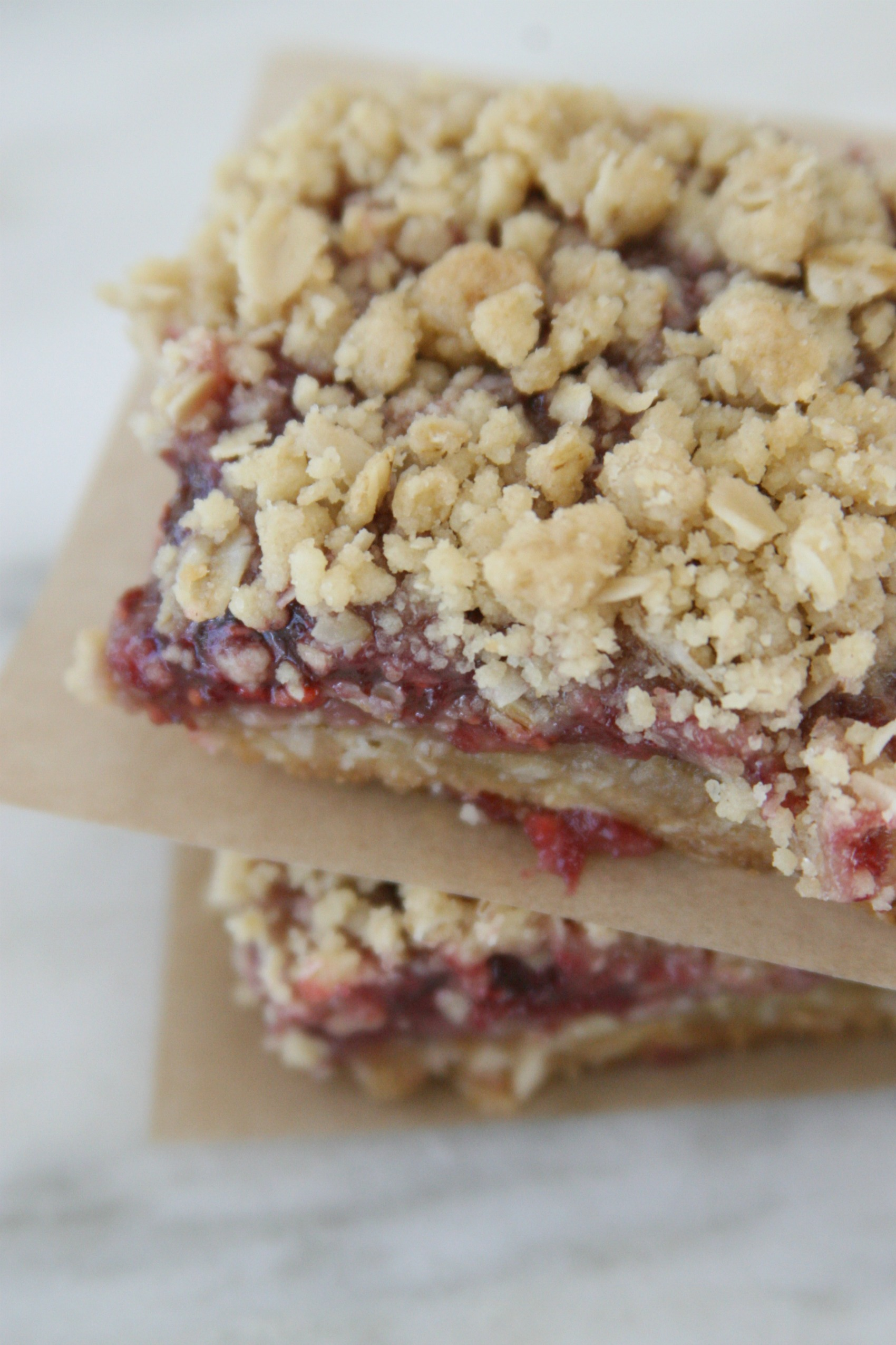 Raspberry oatmeal bars stacked on each other with brown parchment paper in between.