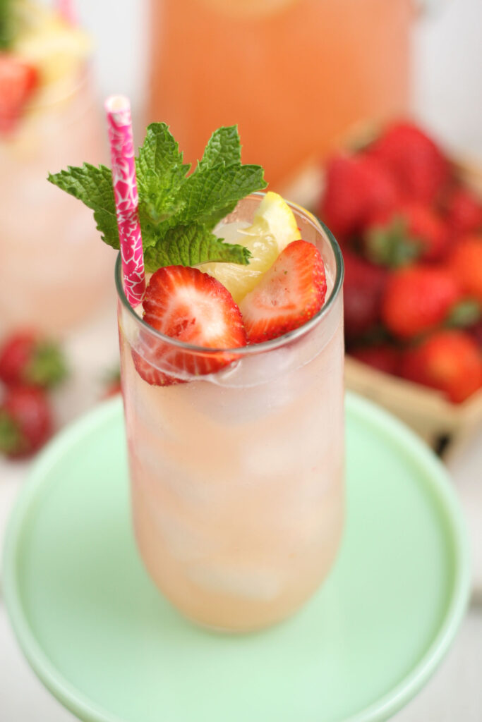 Strawberry lemonade in a glass with fresh strawberry slices, lemon slices, and fresh mint