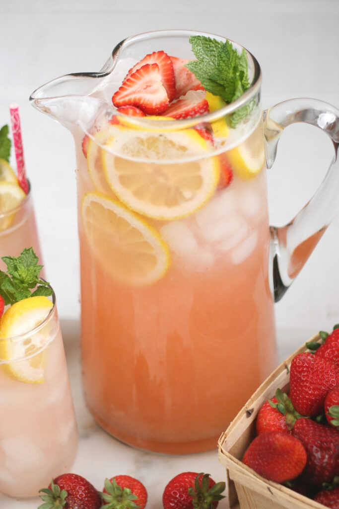 glass pouring pitcher of strawberry lemonade