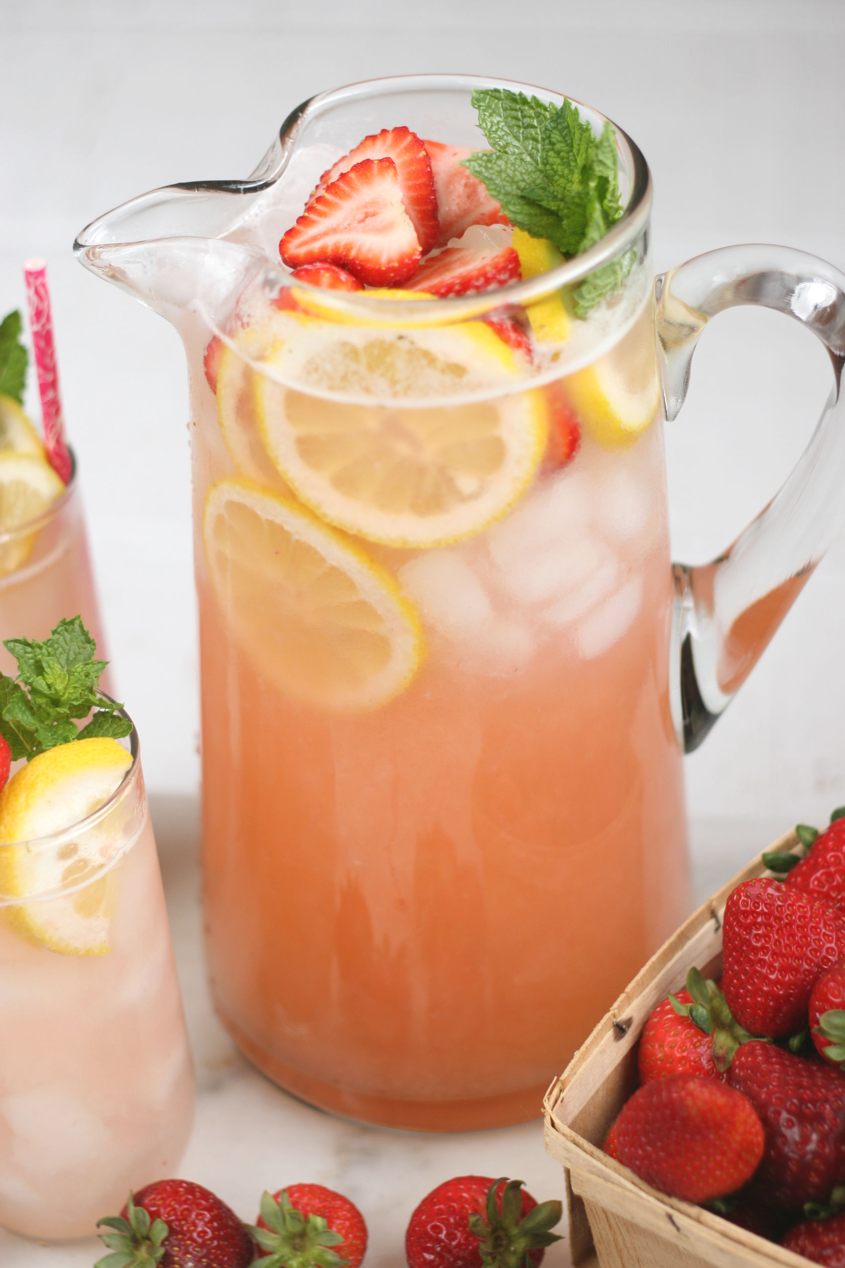 glass pouring pitcher of strawberry lemonade.
