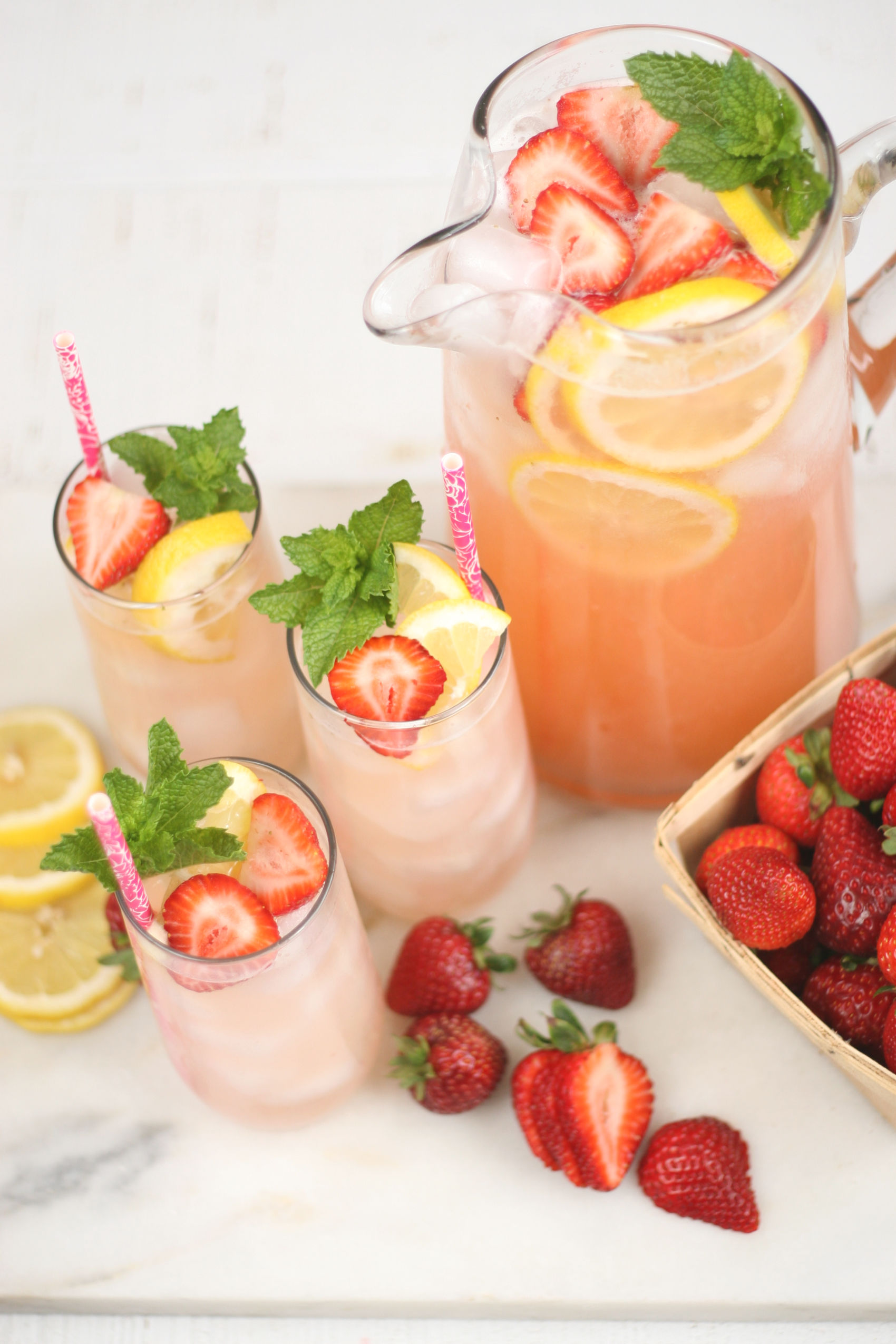 Homemade Lemonade in a glass pouring pitcher with glasses to the side.