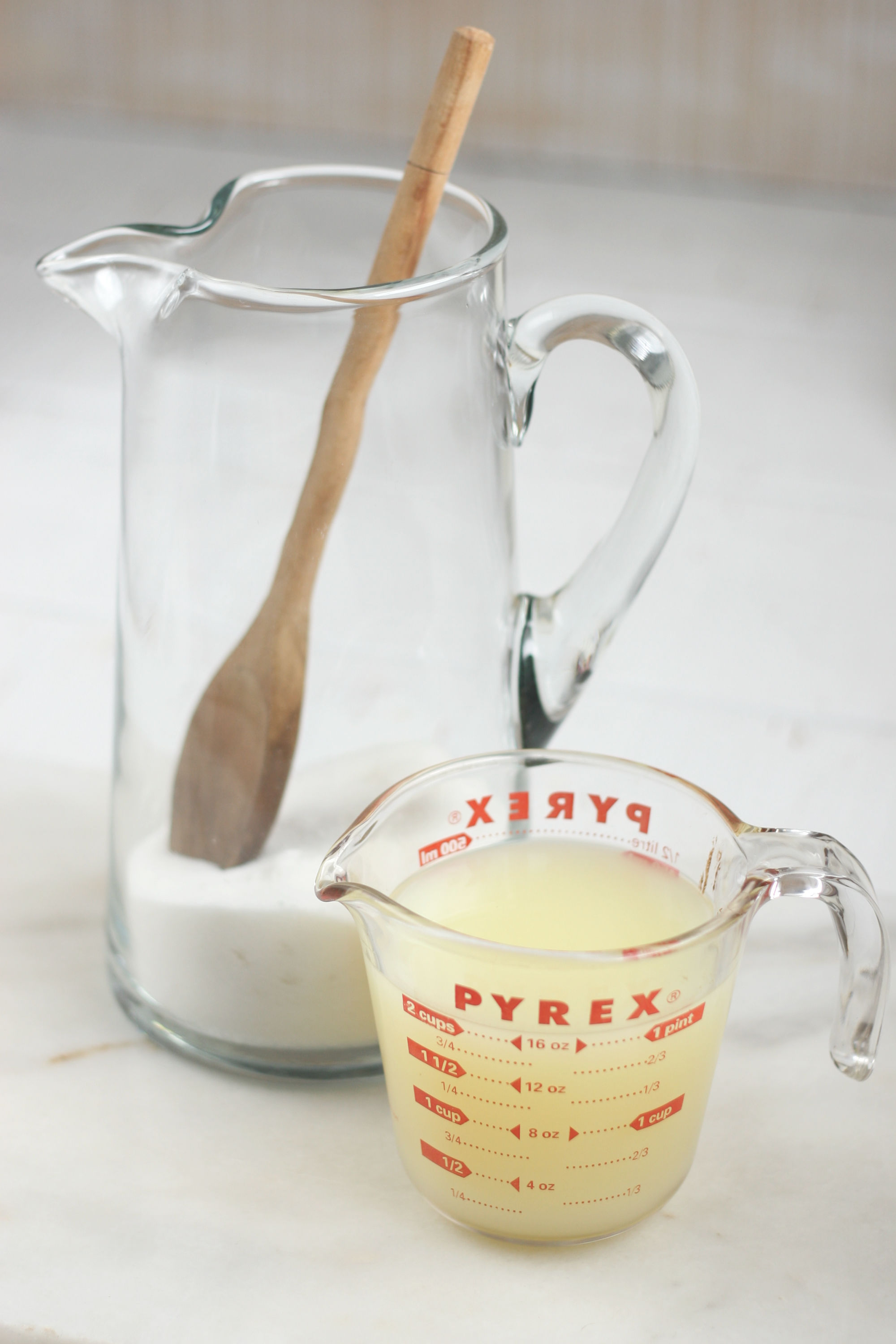 glass pouring pitcher with sugar and measuring cup with lemon juice.
