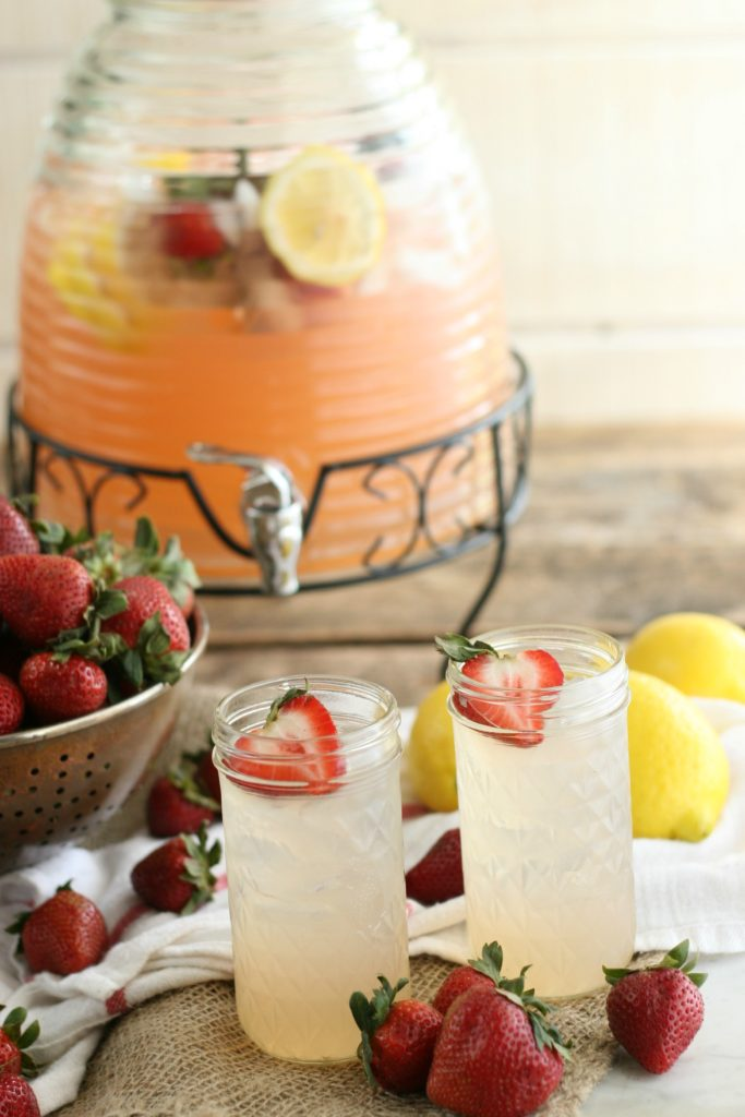 Strawberry lemonade in clear glass drink dispenser with collander of fresh strawberries
