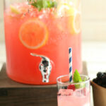 blackberry raspberry lemonade in a glass drink dispenser with glass in front and blue and white paper straw
