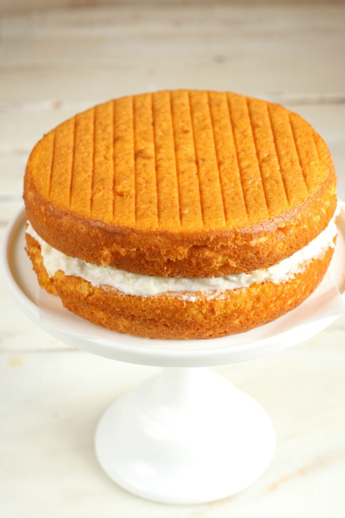 Orange Dreamsicle Cake beginning to be assembled on a white glass footed cake dish and pineapple filling in between layers