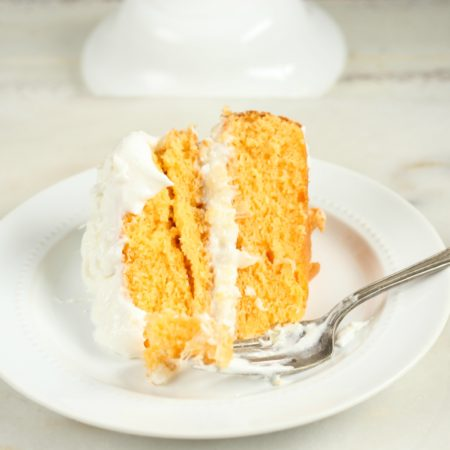 slice of orange dreamsicle cake sitting on a white glass plate with fork on white washed wood