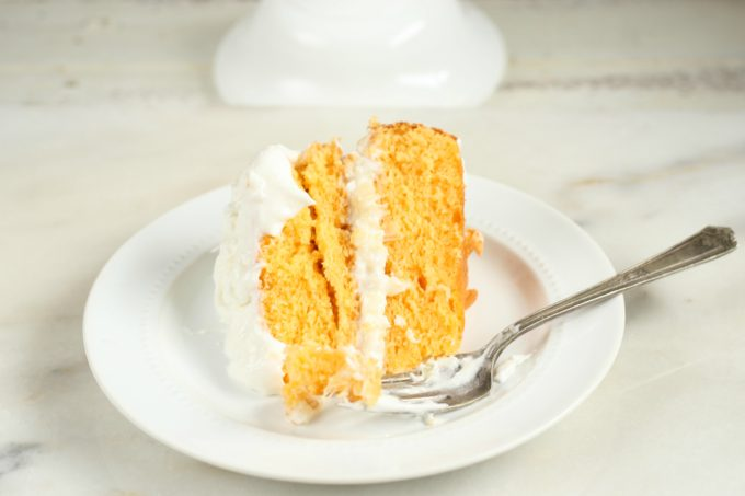 This wonderfully moist Easy Orange Dreamsicle Cake with only a few simple ingredients. Layered with a pineapple and coconut filling. #dreamsiclecake #orangecake #cake #recipes
