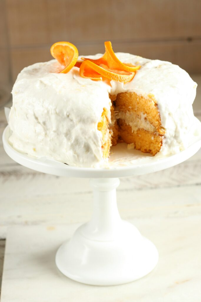 Frosted Orange Dreamsicle Cake sitting on a white glass footed cake dish with one slice cut out and thin orange slices on top of the cake