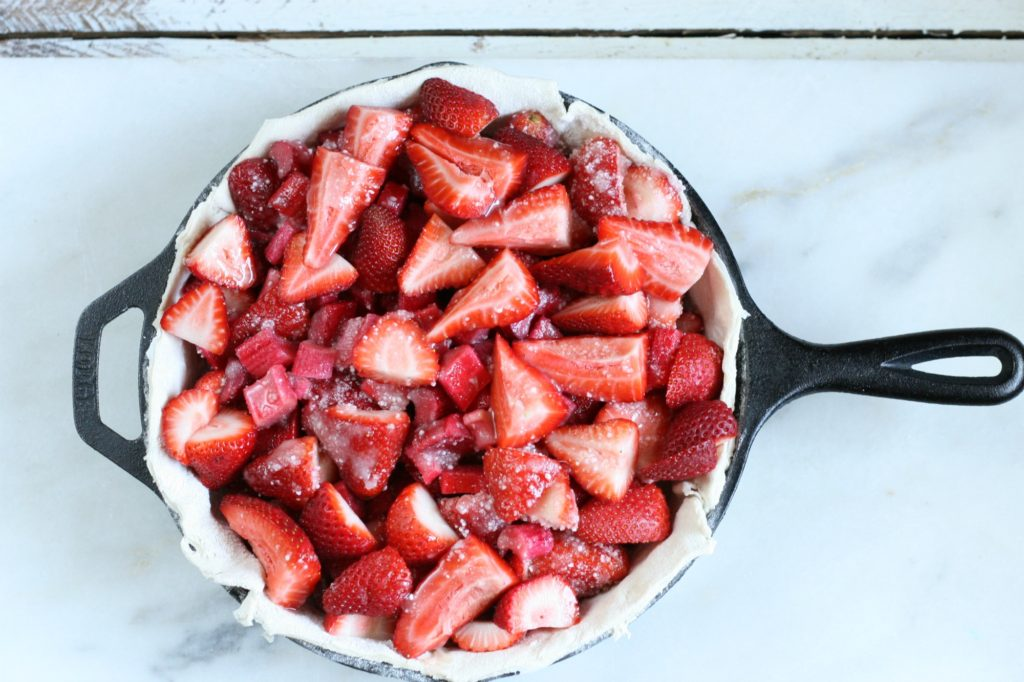 Strawberries and rhubarb piled in an unbaked pie shell in a cast iron skillet