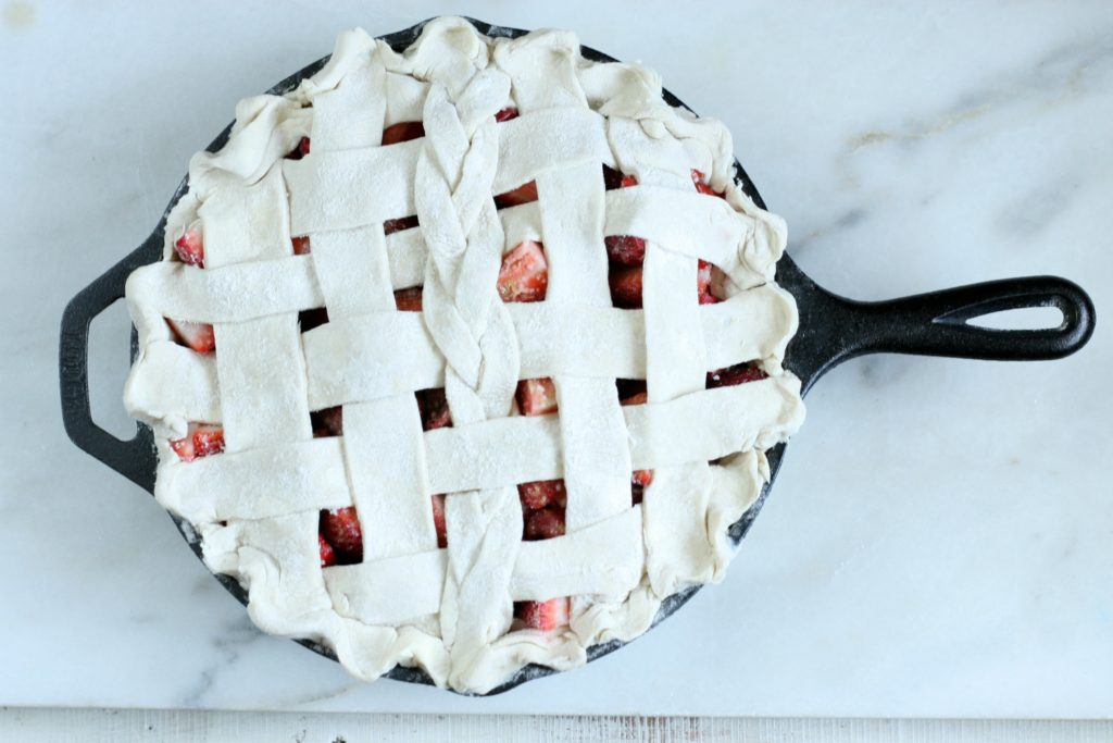 Unbaked strawberry Rhubarb Pie with a weaved crust in a cast iron skillet