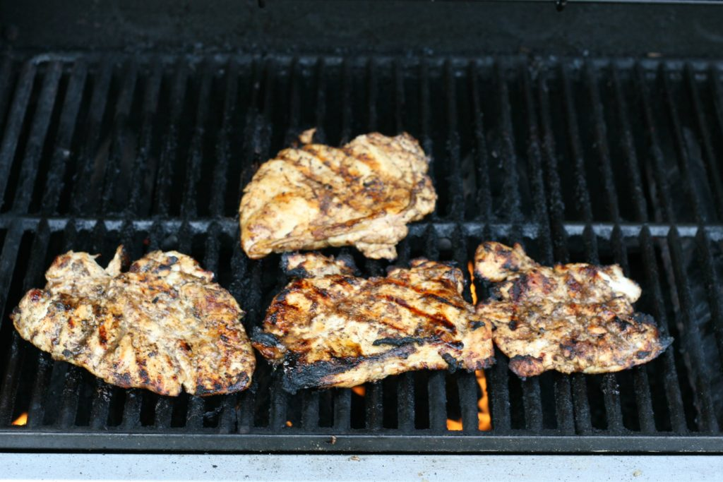 Blood orange and brown sugar boneless skinless chicken breasts cooking on a gas grill.