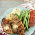 grilled pork chops on light blue plate topped with butter, slices of heirloom tomatoes and fresh green beans to side