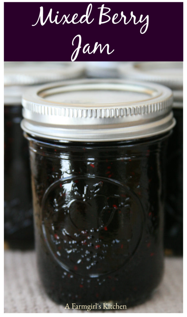 Homemade mixed berry jam in Mason jelly jars, sitting on light oatmeal color kitchen towel cooling.