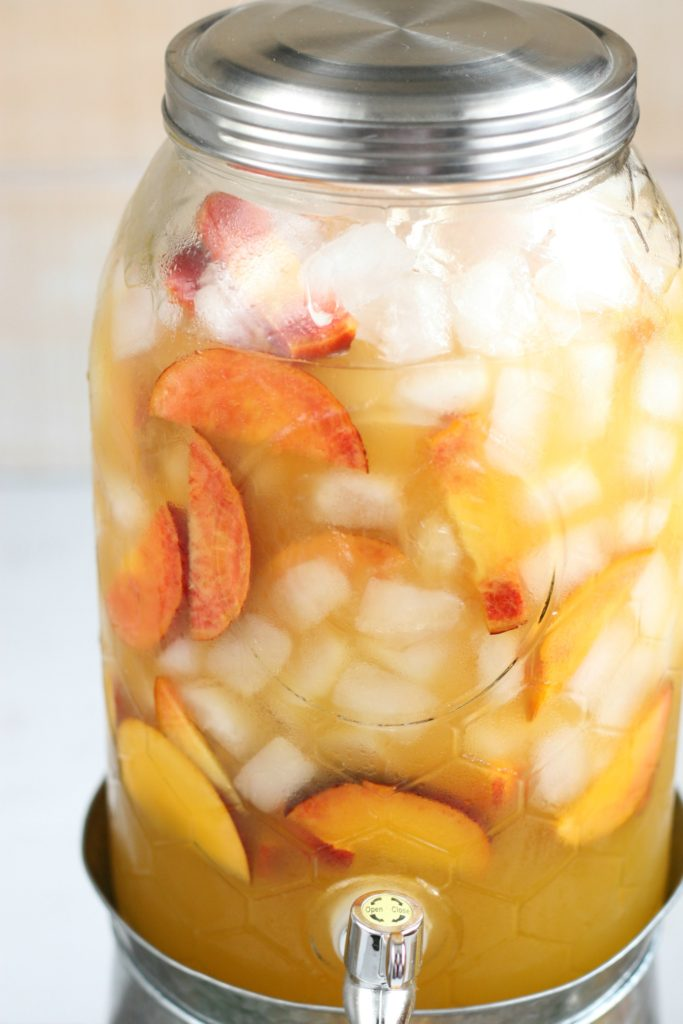 Close up of glass drink dispsenser filled with summer sangria, ice cubes, and peach slices